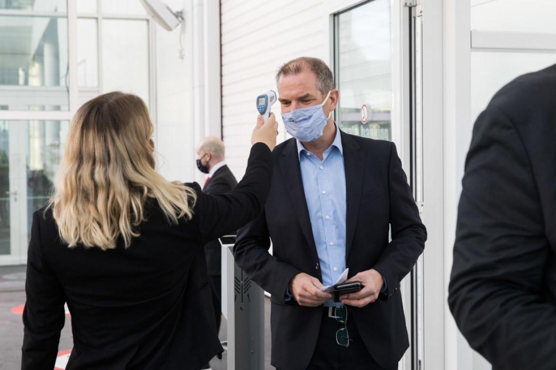 Hostess misst Körpertemperatur eines Gastes: Auch diese Maßnahme ist Teil des Hygienekonzepts auf dem private banking kongress.