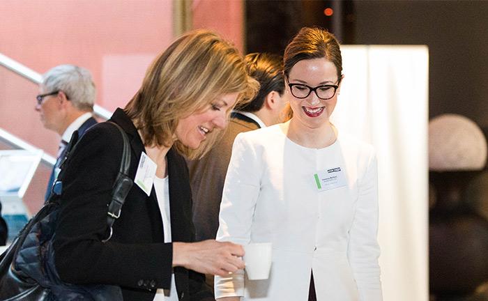 Alexandra Brunner (l.) von Merck Finck & Co und Vanessa Matheis vom Multi Family Office Auretas Family Trust stärken sich mit einem Kaffee, bevor es zum ersten Vortrag geht.