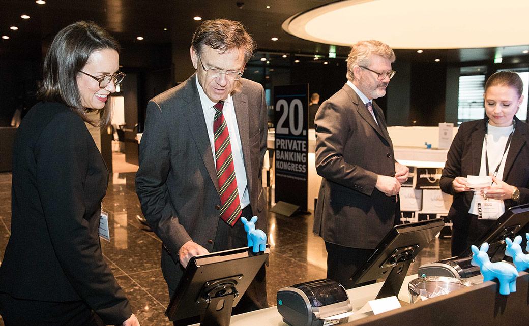 Die Gäste des 20. private banking kongress in Wien treffen an der Registrierung ein.