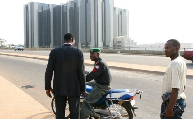 Ein Polizist patrouilliert nahe der nigerianischen Zentralbank in der Hauptstadt Abuja: Nigeria gilt als einer der interessantesten Aktienmärkte Afrikas. Zahlreiche Titel gehören zu den günstigsten der Welt - zumindest nach fundamentalen Kennzahlen.|© BlOOMBERG