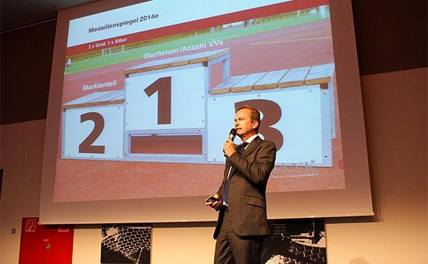 Jens Hagemann, Vorstandssprecher der V-Bank, auf dem 4. Münchner Vermögenstag. Im Hintergrund sieht man die ambitionierten Ziel seines Instituts.