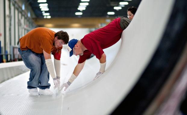 Arbeiter richten eine Naht zwischen Fiberglas-Schichten in einem Werk für Rotorblätter in Newton, Iowa. Die Rotoren sind für Windturbinen von General Electric. Die Anleihe des Technik-Giganten ist unter Anlegern beliebt und die drittgrößte Position im Rentenfonds Kames Strategic Global Bond|© Bloomberg