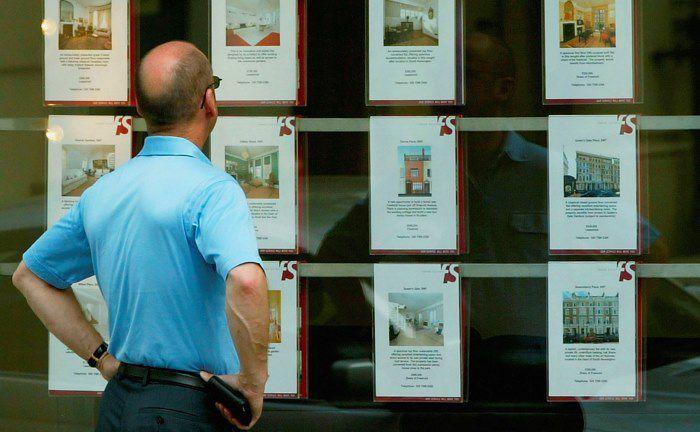 Im Fokus des Interesses: Ein Passant studiert die Immobilienangebote eines Maklers.