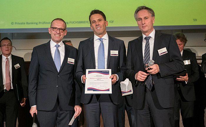 Robert Hager (M.), Bereichsleiter Private Banking des Bankhauses Spängler, nimmt die Auszeichnung von Jörg Richter (l.), Chef des Analysehauses Dr. Richter IQF, und Ralf Vielhaber, Geschäftsführer und Herausgeber des Fuchsbriefe-Verlages, entgegen.