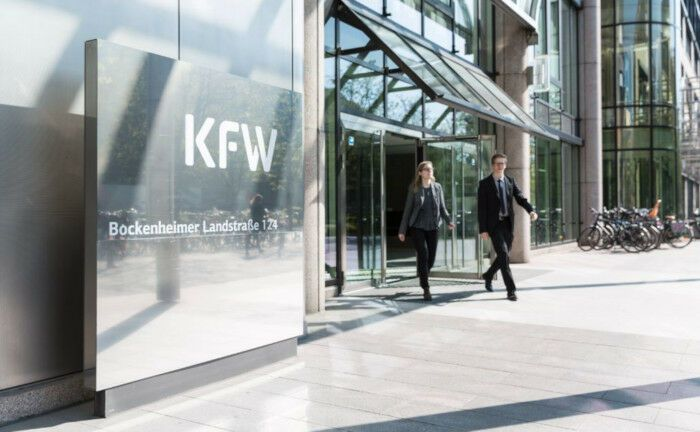 Zwei Mitarbeiter kommen aus dem Eingang der Nordarkade der KfW-Zentrale in Frankfurt. Die Förderbank KfW ist der wichtigste Emittent grüner Anleihen in Deutschland. |© KfW-Bildarchiv Thorsten Futh