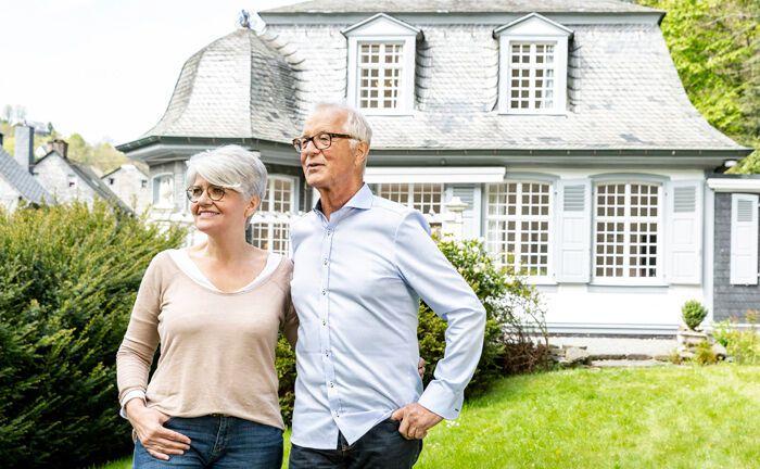 Älteres Ehepaar vor ihrem Eigenheim: Bei einer Nießbrauchimmobilie verkaufen die Eigentümer das Objekt unter Marktwert und erhalten im Gegenzug ein insolvenzfestes Wohn- und Nutzungsrecht.|© imago images / Westend61