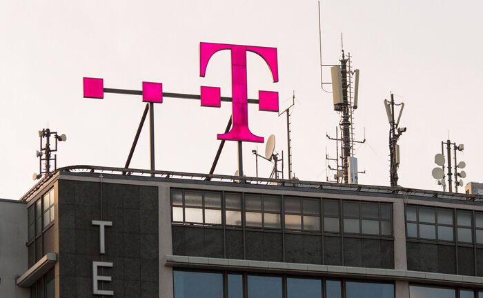 Logo der Deutschen Telekom auf einem Berliner Hausdach: Die Aktie des Dax-Unternehmens gibt es jetzt auch als auf der Blockchain abgebildetes digitales Wertpapier.|© imago images / Dirk Sattler