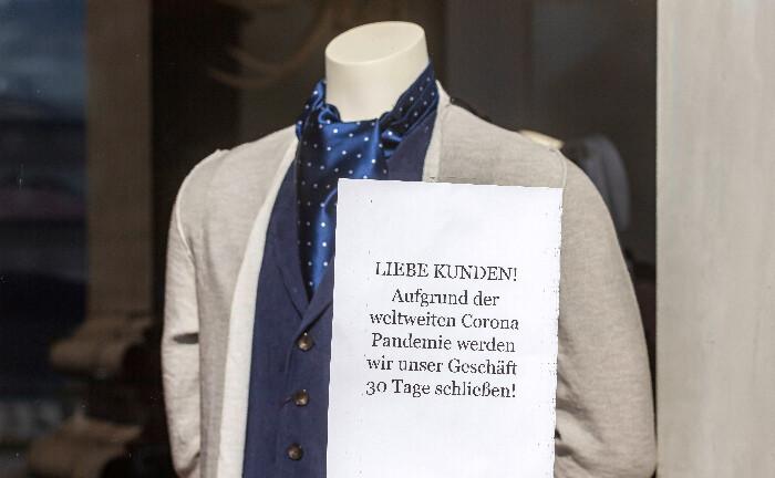 Hinweis für Kunden: Ein Stuttgarter Bekleidungsgeschäft muss vorübergehend schließen. Die Auswirkungen der Corona-Krise auf gesellschaftliche Verhaltensweisen sind kaum abzusehen, dennoch wird die Wirtschaft durch Nachholeffekte auch wieder zulegen.|© imago images / Arnulf Hettrich