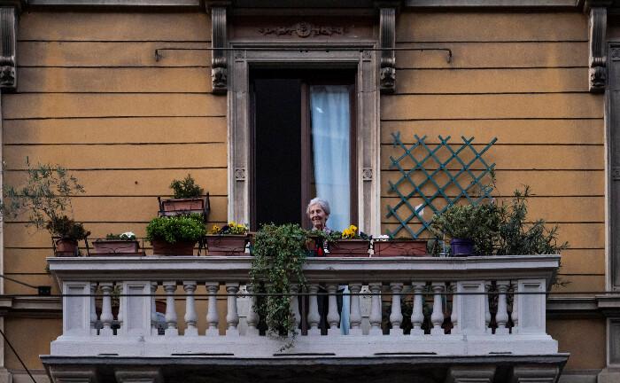 Eine ältere Dame hört angesichts der Corona-Kontaktsperre Musik auf ihrem Balkon in Porta Genova: Das Corona-Virus sorgt für eine neue Form von gesellschaftlichem Zusammenhalt, und das nachhaltig, glaubt Matthias Horx.|© imago images / ZUMA Wire