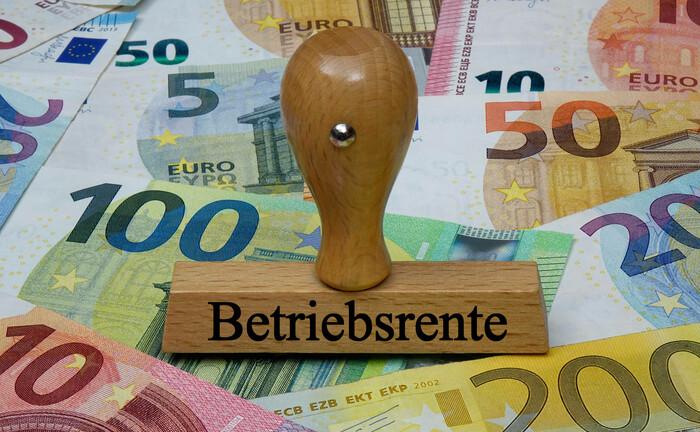 Auf Geldscheinen steht ein Stempel mit dem Schriftzug Betriebsrente: Ab 1. Januar 2022 erhalten Versorgungsberechtigte den vollen PSV-Schutz für den Fall, dass die bAV-Leistungen von der Pensionskasse gekürzt und der Arbeitgeber insolvent wird.