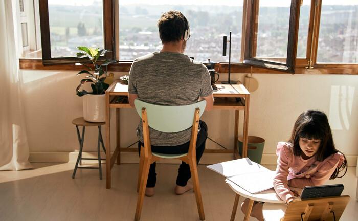 Während ein Mann zu Hause arbeitet, erledigt seine Tochter Hausaufgaben: Auch Pensionskassen haben ihre Mitarbeiter in der Corona-Krise ins Homeoffice geschickt.