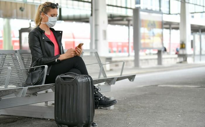 Eine Frau mit Mundschutzmaske wartet auf ihren Zug: Mitarbeiter der Deutschen Bank sollen künftig bei Geschäftsreisen die Bahn nehmen. |© imago images / Michael Weber