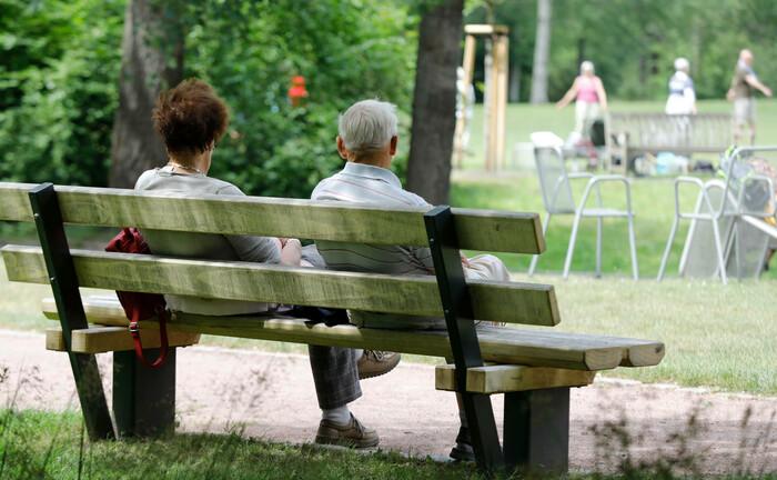 Zwei Rentner sitzen auf einer Bank und beobachten andere Senioren bei Gymnastikübungen: Das Sozialpartnermodell erwies sich bislang als Ladenhüter.
