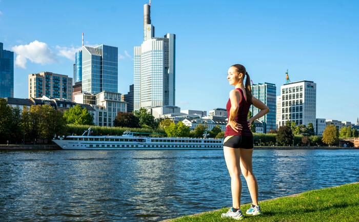 Eine junge Frau steht am Ufer des Mains und blickt auf das Zentrum der Bankenmetropole Frankfurt: Das Versorgungswerk der Landesärztekammer Hessen sucht am Standort Frankfurt eine Fachkraft für ihre Kapitalanlage.