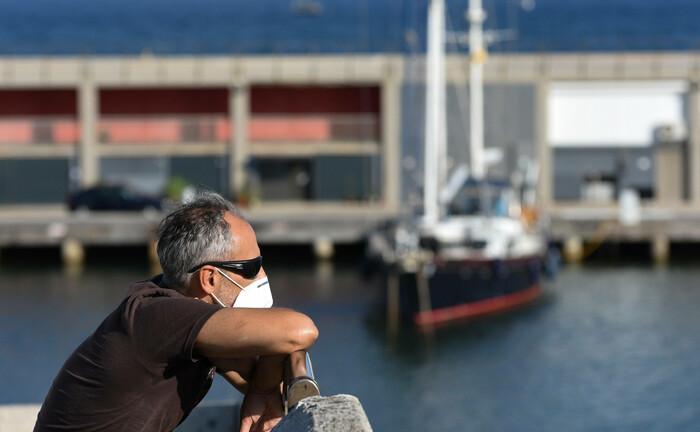 Ein Mann trägt einen Mund-Nasen-Schutz: Aufgrund der Krise sinken die Einstiegspreise für Unternehmensbeteiligungen.  |© imago images / ZUMA Wire