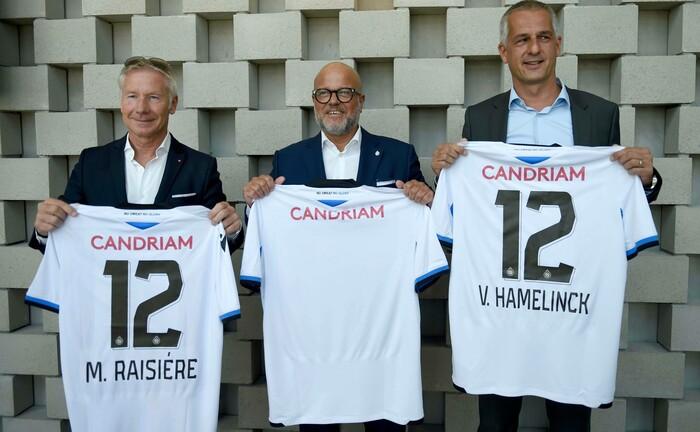 Marc Raisière, CEO bei Belfius, Bart Verhaeghe, Präsident des FC Brügge und Vincent Hamelink, Investmentchef bei Candriam (v.l.) bei der Vorschau des neuen FC Brügge Trikots: Candriam engagiert sich abseits der Vermögensverwaltung unter anderem in Fußballvereinen.