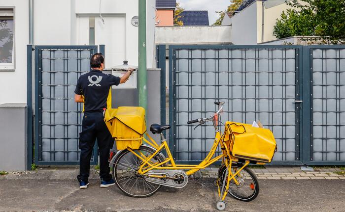 Ein Fahrrad-Postbote steckt Briefe in den Briefkasten eines Essener Wohnhauses: Die Zertifizierungen für Finanzplaner überreichte der FPSB Deutschland ebenfalls Corona-bedingt auf postalischem Weg.