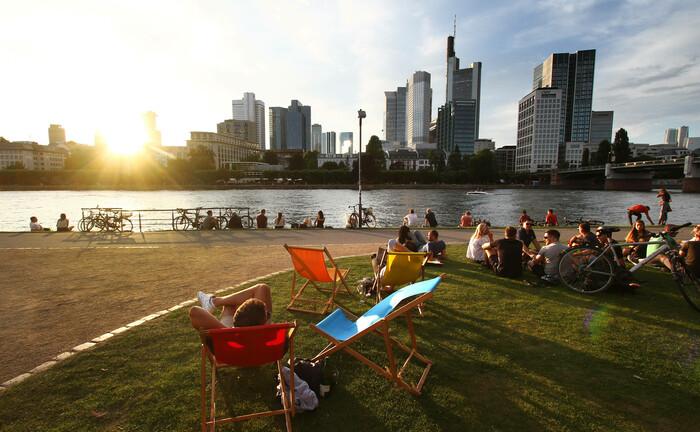 Personen genießen in Liegestühlen die Abendsonne und den Sonnenuntergang am Main gegenüber der Skyline des Bankenviertels in Frankfurt: Banken und Debt-Fonds bieten Mittelständler wieder günstigere Kredite an. |© imago images / Ralph Peters