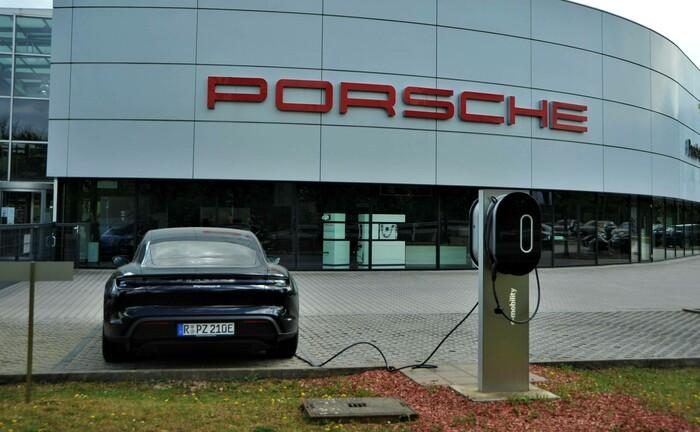 Ein Porsche Taycan steht an einer Strom-Ladesäule: Die Zuffenhausener Sportwagenschmiede hat im vergangenen Jahr einen grünen Schuldschein emittiert; der Erlös fließt unter anderem in die Entwicklung elektrischer Fahrzeuge.  |© imago images / Manfred Segerer