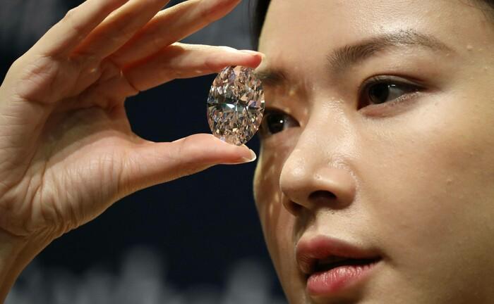 Ein Model betrachtet den Diamanten mit 102,39 Karat: Ein Sammler aus Japan hat den Edelstein ersteigert.