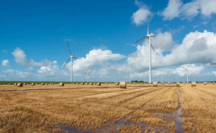 Ackerfläche mit Windkraftanlagen: Beim Impact Investing werden Projekte und Unternehmen unterstützt, die nachhaltige Ziele verfolgen.|© imago images / penofoto
