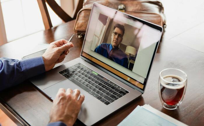 Mann sitzt mit Hemd und Krawatte vorm Laptop