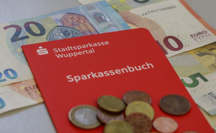 Bargeld und ein Sparkassenbuch der Stadtsparkasse Wuppertal