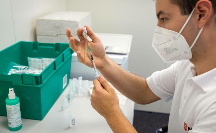 Ein Ärzt bereit eine Corona-Impfung im Impfzentrum Aichtal vor