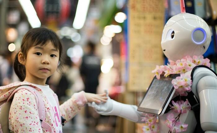 Japanisches Mädchen schließt Freundschaft mit einem Roboter: Künstliche Intelligenz und maschinelles Lernen können auch bei der Bewertung von ESG-Kriterien helfen.|© Unsplash / Andy Kelly